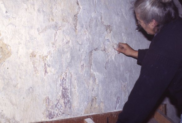 Moment of discovery. Ann cleans the 16th century limewash covering the 13th century figure.  The scene was probably hidden as part of the Reformation when decoration within churches was painted over.
