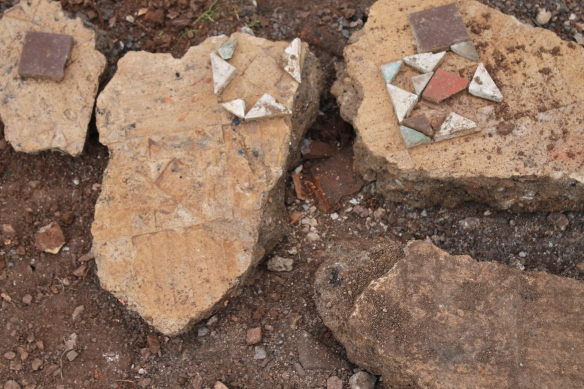 Slabs of broken cement flooring with the impressions of the lost tile floor. The many coloured tile pieces fit into the impressions.