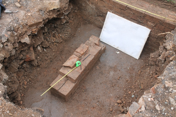 Drawing the middle trench after excavation. Note the bluey grey colour painted onto the floor and the rendered brick wall behind he drawing board.