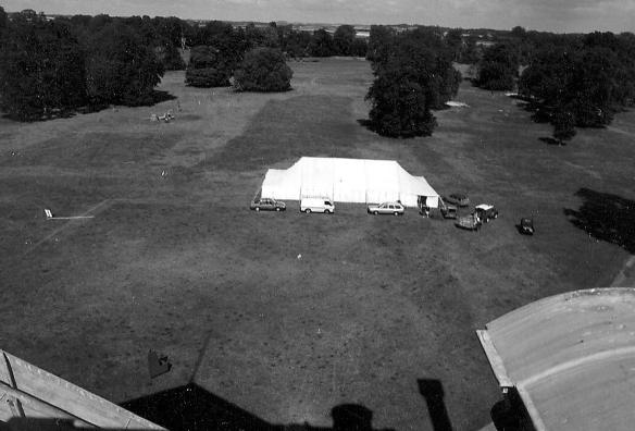 The north view from the roof in 1990. Beyond the tent is the darker line of the wide central vista. On the right of this just above the tent is a chestnut tree and right of this is a circular earthwork, the footings of a classical temple folly. The tree was planted on a raised path running parallel with the drive.  Sarah thinks that in the 18th century visitors to the house  would approach along this path rather than spoil the prospect from the house by bringing their carriages along the central drive. The tree was planted to break up the straight line of the path when the less formal Capability Brown naturalised landscape park movement was in vogue. Left of the tent is a fallen tree blown over in the January 1990 storm. This revealed old Kingston Lacy in its roots.