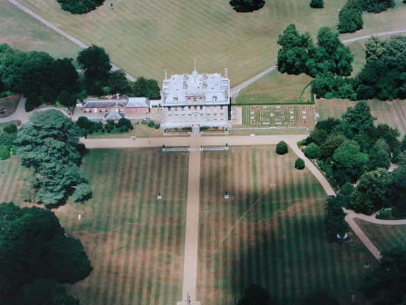 The parch marks of the south lawn. The dots along the left side of the picture are our supposed avenue of trees. The early 19th century path to the Egyptian obelisk cuts across traces of an 18th century rectilinear arrangement of paths and lawns but the pale markings running diagonally from the obelisk to the trees on either side may represent remains of a garden design of the 1660s. The Teddy Bear's Picnic was under the shade of the trees to the right.