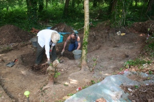 Two volunteers uncover the floor of the pottery in trench D.