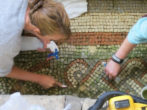 AC and Susie using toothbrushes to clean the mosaics