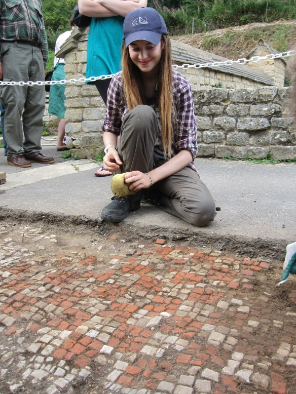 Harriet sponging the mosaic to clean the last of the soil of them and bring out the colours.
