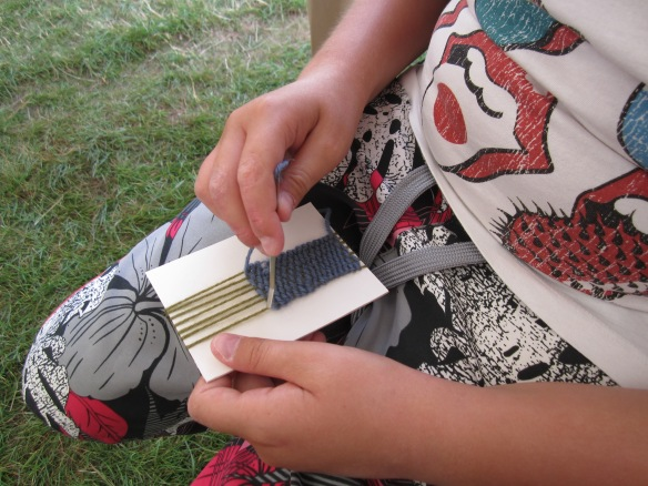 Weaving a wrist band, a very popular activity with girls and boys alike