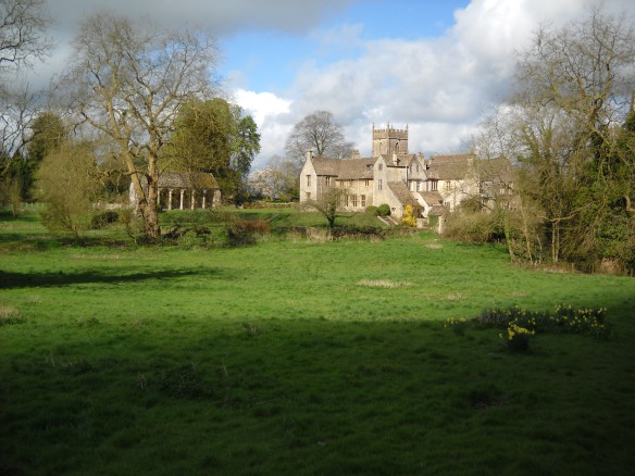 Horton Court beside the parish church on a spring line at the foot of the Cotswold escarpment. An ancient settlement location, the Iron Age Horton Camp hillfort lies on the ridge top behind the camera location. The Tudor loggia can be seen on the left with the terraces of the Tudor garden stepping down to the stream and the line of medieval fishponds beside the house.