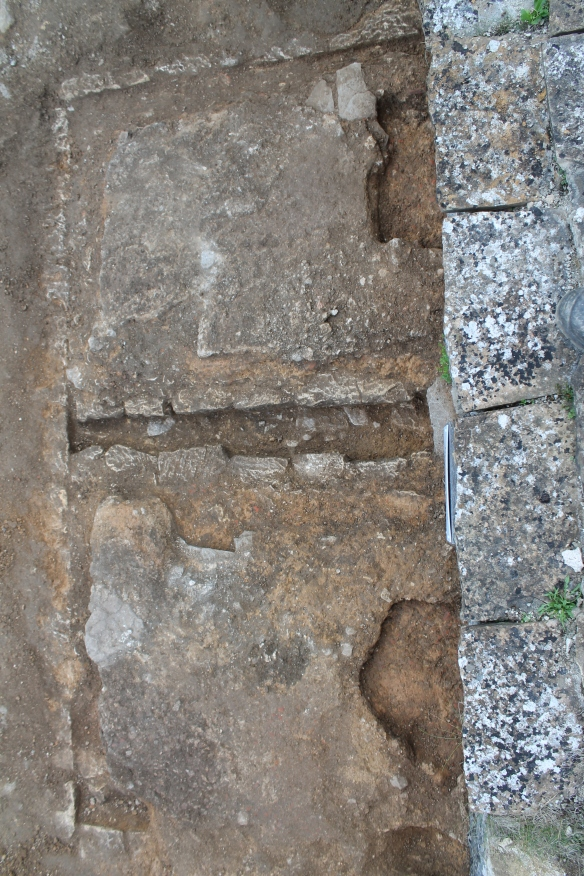 The surviving mortar floor cut by two shallow post-holes the lower hole contained our sherd of samian.