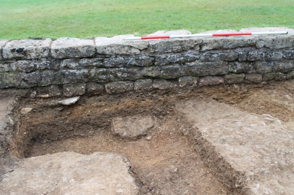 The Roman courtyard layers continuing under the Victorian revetment wall.