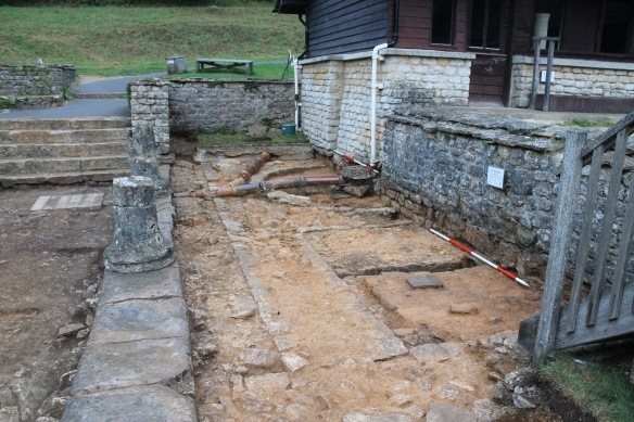 The support wall for the columns built on a foundation of stone with the raft of mortar and rubble butting against it on the north.  This covered the footings of the old baths before Professor Richmond excavated and revealed the walls. The flight of steps and the walls abutting them were all proved to be Victorian or later in date.