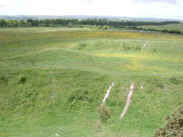 The view from Badbury's west gate across the Roman temple along the Dorchester road to the group of three barrows by the entrance track.