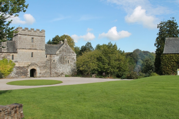 Cotehele medieval manor house. Cotehele river front lies below the steep slope of the wooded gardens to the right.