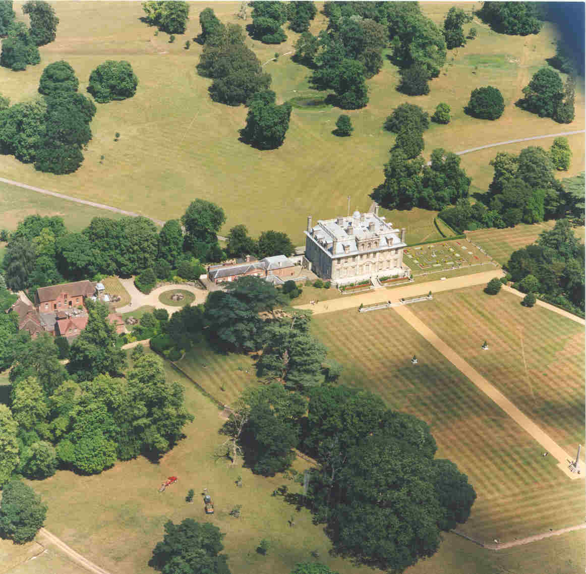 The present house was only built in 1660. The remains of medieval Kingston Lacy lie across the top of the picture as a series of earthworks below the 17th-18th century drives, paths and garden buildings.  The line of the Roman road from Badbury to Hamworthy crosses the park from the top left corner to the upper left side of the photo and prehistoric flint, Roman and medieval have been found across the park. The old tree that revealed the manor house fell half way between the 1660s mansion and the top left corner of the picture.