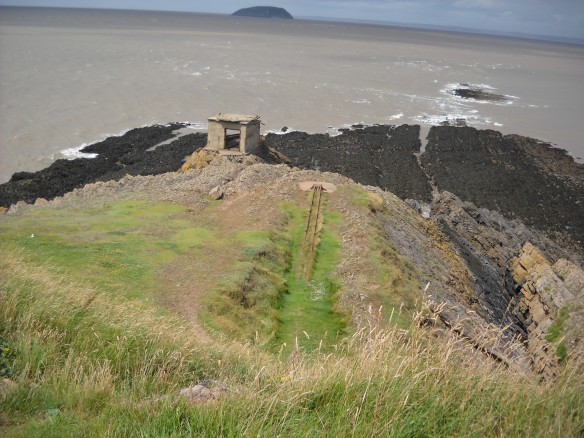 Beyond the gun battery is the rocky headland with the view towards the islands of Flat Holm and Steep Holm in the Channel. A WWII searchlight building can be seen. Part of its roof has been flipped back by a violent storm. To the right are the rails for an experimental rocket launcher created by the 'wheezer and dodger' boffins based in a requisitioned pier in Weston-Super-Mare.