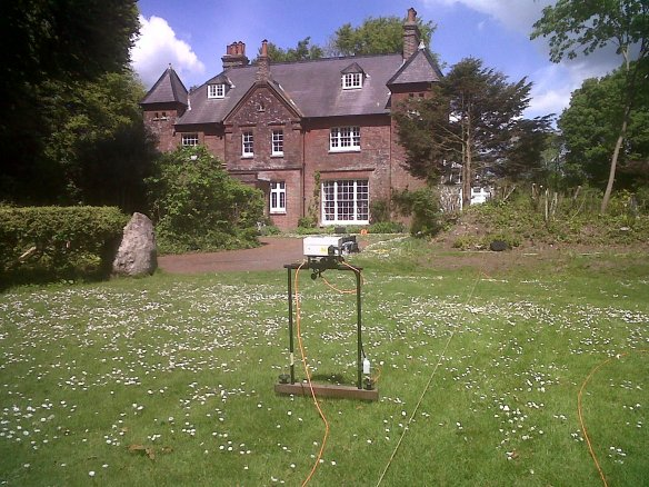 The refurbished resistivity meter beside the stone found during the 1980s excavations.