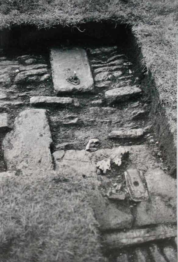 A small trench in the middle of the lawn in the west garden discovered the  gateway to the inner garden and the pitched stone straight entrance track leading to it. Bottom right is the central socket for holding the ornate double-leaved gates in place. Top left is a raised metal fixing for holding a gate in place when open. One of the stones had been part of a window reused from an earlier house.