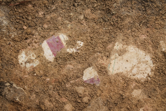 Red and blue lines on cream. Part of a rubble base thrown down on which the mosaic was laid.