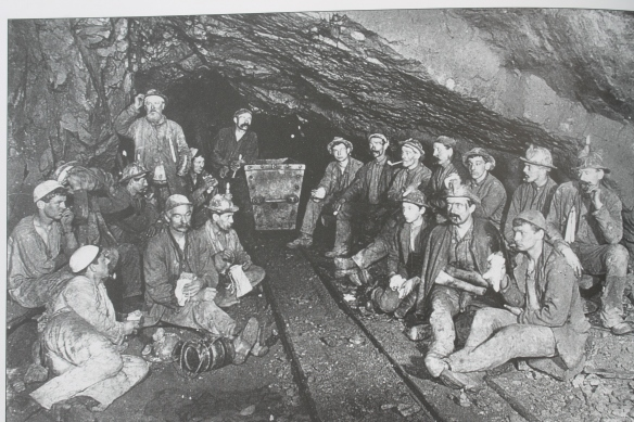 Tin miners at Cook's Kitchen Mine 1893 during a lunch break 'croust'. Their light is produced by candles fixed to their helmets with lumps of damp clay. Miners would take advantage of the fine acoustics and sing hymns down the mines
