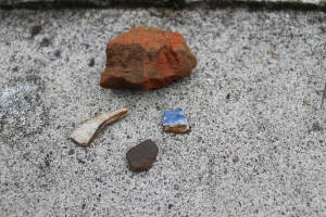 One of our chunks of brick and below it the two fragments of post-medieval pottery we found, typical white ware and blue and white wares of the late 18th to early 19th century. Below them, the black blob is a late prehistoric piece of pottery over 2000 years old.