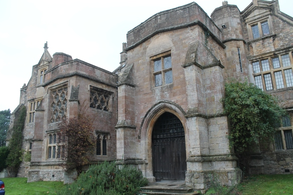 The south front with its 14th century porch and to the left of it the decorated windows of the late medieval 1st floor chapel.