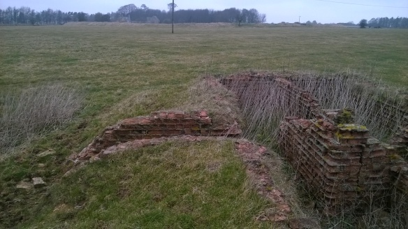 View towards the rampart of Windrush Iron Age hillfort from the weathered brickwork of a WWII building.
