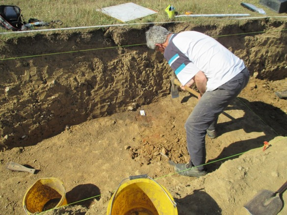 The feature can be seen as a red and dark brown black area next to the side of the trench