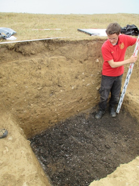 Alex taking a level before bagging up a sample of  the mound material