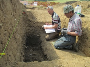 Martin recording the ditch with help from Rob who dug it