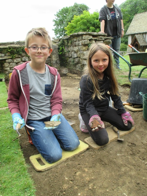 Sammy and shanon with their best finds, a large fragment of tile and the piece of stone roof tile