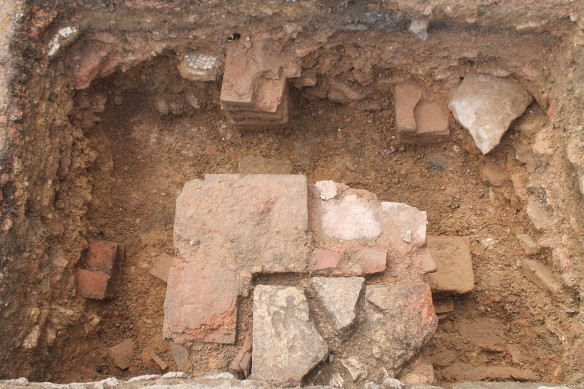Trench A looking west. On the last day we could see four tile pilae emerging from the mosaic and painted plaster rubble filling of the hypocaust. The stone core of the feature in the bottom centre of the photo was keyed into the east wall of 21 and later surrounded with a coursed tile edging.