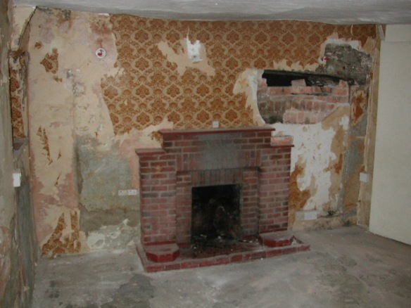 Buildings like Uvedales have been repaired and adapted over 100s of years. Here a modern fireplace in the east sitting room of the central ancient Uvedales stack is only the latest in a nest of fireplaces which, like Russian dolls, have filled up the space within the the original inglenook.It can be seen emerging from under the wallpaper.