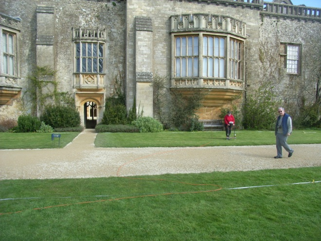 Looking north. Lacock's 2008 south park and monastic church resistivity survey in action . Meg and Tony are standing on the church site which became a Tudor garden beneath Fox Talbot's ornate 19th century windows.These windows were built into the monastic church cloister wall. The T junction of paths in the photo can be seen as blue bands on the resistivity plot (next image). The narrower path leads through a door beneath the smaller window into the cloisters.