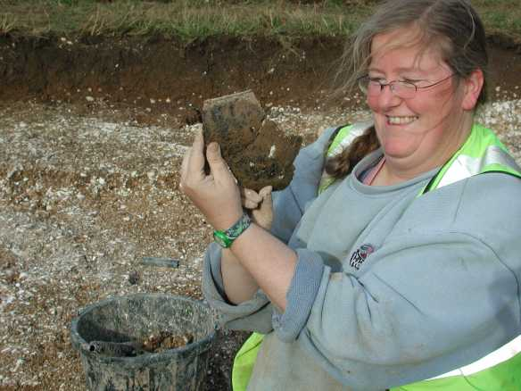 A very happy archaeologist in a trench at Badbury Rings with a large sherd of Iron Age pottery