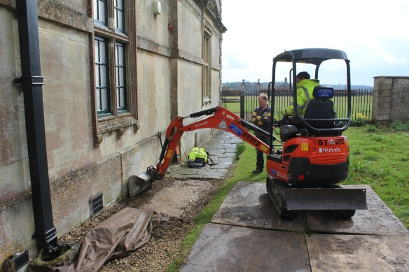 Mini-digger digs down to find the blocked door.