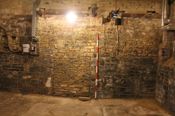 The mysterious blocked door in the cellar. The ranging pole divisions are 0.2m and at 1.7m up you can see that the doorway and blocking has been removed and the wall rebuilt in the 19th century. Note the vent top right can be seen in the next photo outside to the left of the mini-digger.