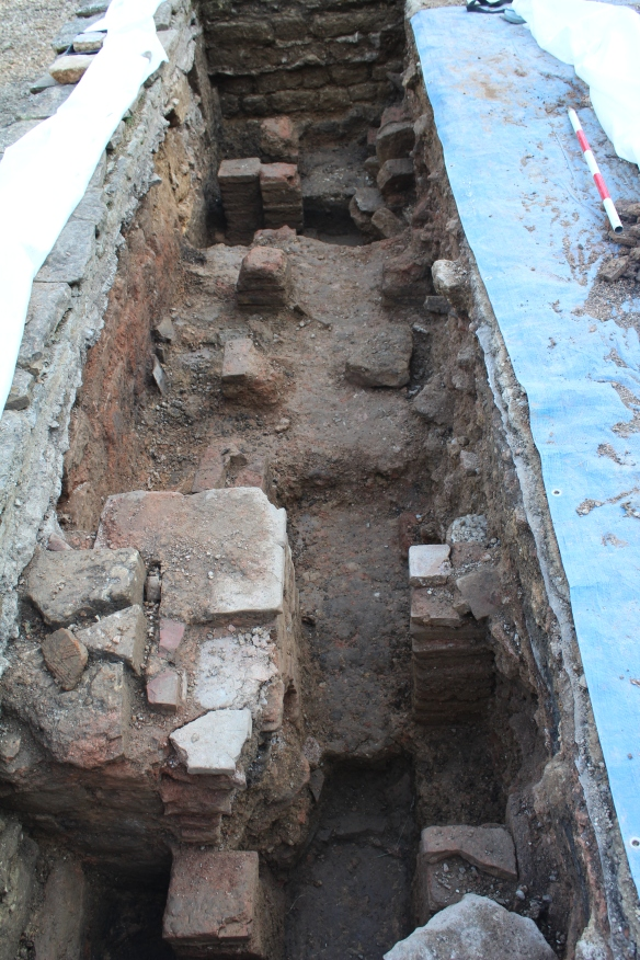 The two lines of pilae on the east side of room 21. The blocked door is top right. The burnt plaster lines the wall along the left side of the photo. A broken channel of box flue tiles was attached to this wall. Part of the later heating system.