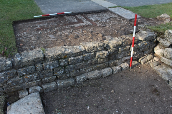 The mosaic forming the SE corner of the reception hall and the top right the door threshold into the north corridor. Below this is the wider revetment wall of the north range. No doorway visible from the East Gallery but the offset wall at the bottom of the ranging pole is probably where the Roman floor used to be. The flagstones on the left abut the revetment wall and this is a later wall forming the west side of the gallery. On the right is the broad buttress wall which may have infilled an earlier doorway. Our deep interesting trench is on the right side of this.